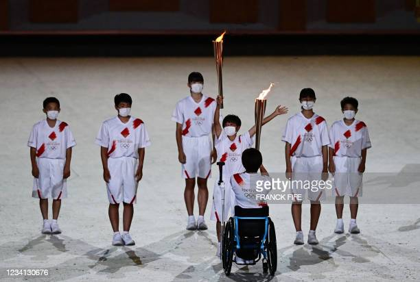 Torchbearer relays the Olympic Flame during the opening ceremony of the Tokyo 2020 Olympic Games, at the Olympic Stadium, in Tokyo, on July 23, 2021.
