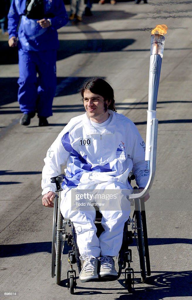 Torchbearer Richard Castaldo carries the Olympic Flame during the 2002 Salt Lake Olympic Torch Relay January 31, 2002 in Littleton, CO. Castaldo was injured in the 1999 Columbine High School shooting.