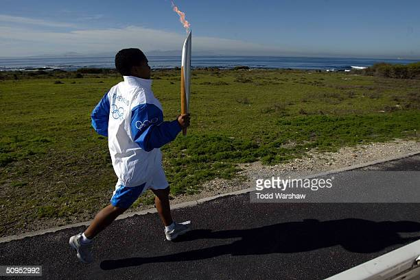 Torchbearer Roeleen Flenner carries the Olympic Flame on Robben Island during Day 9 of the ATHENS 2004 Olympic Torch Relay June 12 2004 in Cape Town...
