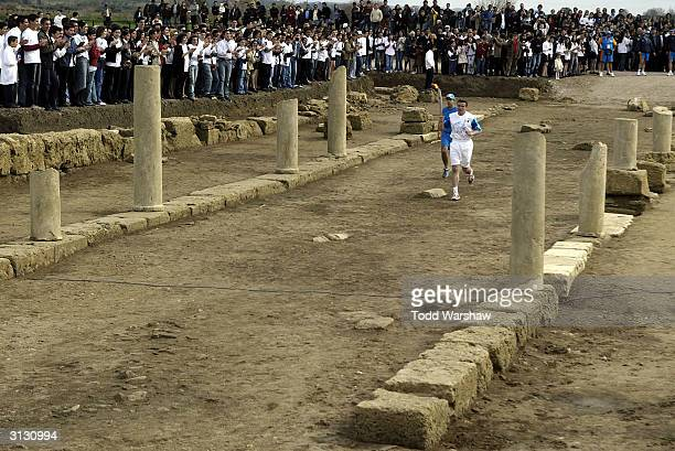 Torchbearer Sergey Bubka former Olympic pole vaulter carries the Olympic Flame into the ancient Theatre of Ilidas during the Greek portion of the...