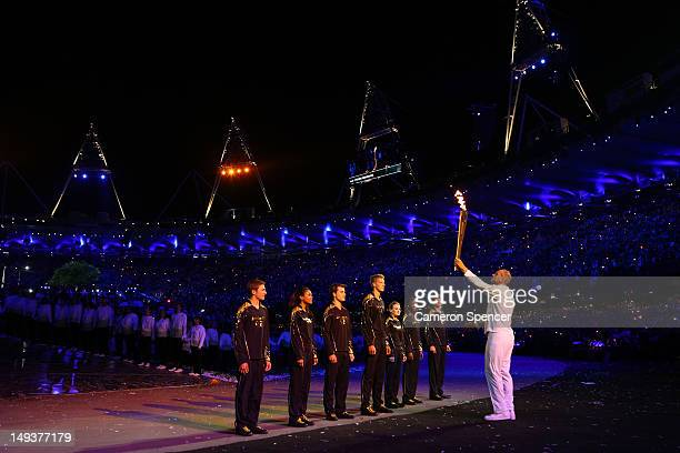 Torchbearer Sir Steve Redgrave hands the Olympic Flame over to seven young athletes who present Britain's hopes for the next Olympics during the...
