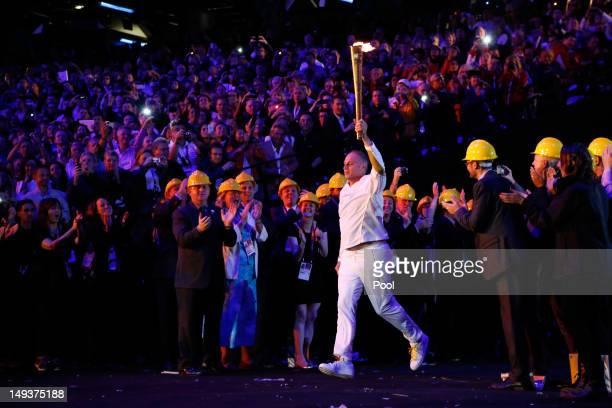 Torchbearer Sir Steve Redgrave jogs as he carries the Olympic Flame during the Opening Ceremony of the London 2012 Olympic Games at the Olympic...