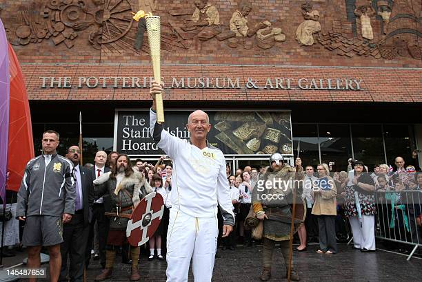 Torchbearer Tony Pulis holds the Olympic Flame outside the Potteries Museum and Art Gallery on day 13 of the London 2012 Olympic Torch Relay on May...