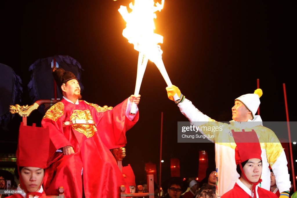 A torchbearer wearing a traditional King's costume carries the Olympic torch in front of the main entrance to Gyeongbokgung Palace during the PyeongChang 2018 Winter Olympic Games torch relay on January 13, 2018 in Seoul, South Korea.