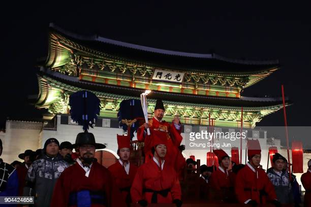 A torchbearer wearing a traditional King's costume carries the Olympic torch in front of the main entrance to Gyeongbokgung Palace during the...