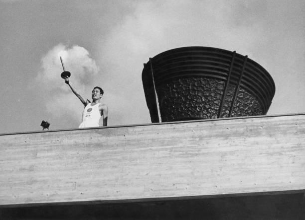 يقف حامل الشعلة بجانب المرجل الأولمبي ، المولود في هيروشيما ، الذي ...