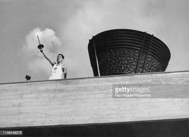 Torchbearer Yoshinori Sakai , who was born in Hiroshima on the day the atomic bomb was dropped on the city, stands beside the Olympic cauldron as he...