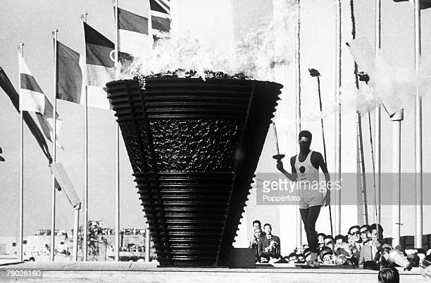 Torchbearer Yoshinori Sakai , who was born in Hiroshima on the day the atomic bomb was dropped on the city, stands beside the Olympic cauldron after...