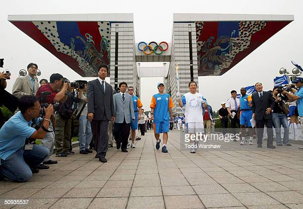 Torchbearer YunTaek Lee carries the Olympic Flame through the World Peace Gate during Day 5 of the Athens 2004 Olympic Torch Relay on June 7 2004 in...