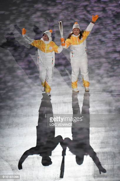 Torchbearers hold the Olympic flame during the opening ceremony of the Pyeongchang 2018 Winter Olympic Games at the Pyeongchang Stadium on February 9...