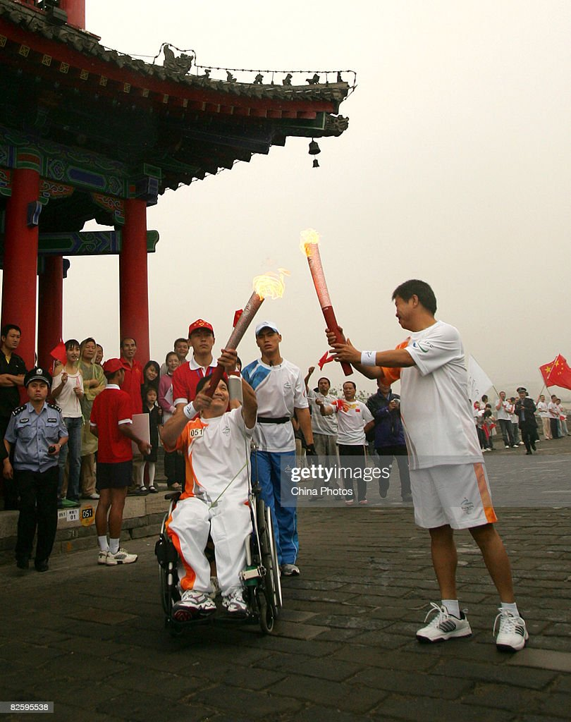 Torchbearers pass on the Paralympic flame during the Beijing