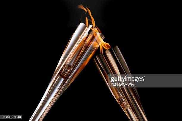 Torchbearers transfer the Olympic flame during during the arrival ceremony of the Tokyo 2020 Olympic Torch Relay in Tokyo on July 23 ahead of the...