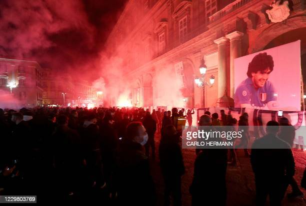 Torches are lit on Piazza del Plebiscito in Naples on November 26, 2020 as people gather to mourn the death of late Argentinian football legend Diego...