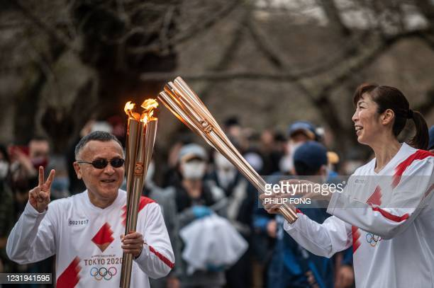 Torches held by Masamitsu Kikuchi and Motoko Obayashi are seen on the last stage of the second day of the Tokyo 2020 Olympic Games torch relay at...