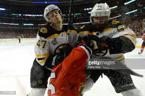 Torey Krug and Johnny Boychuk of the Boston Bruins check Andrew Shaw of the Chicago Blackhawks in Game Five of the 2013 NHL Stanley Cup Final at...
