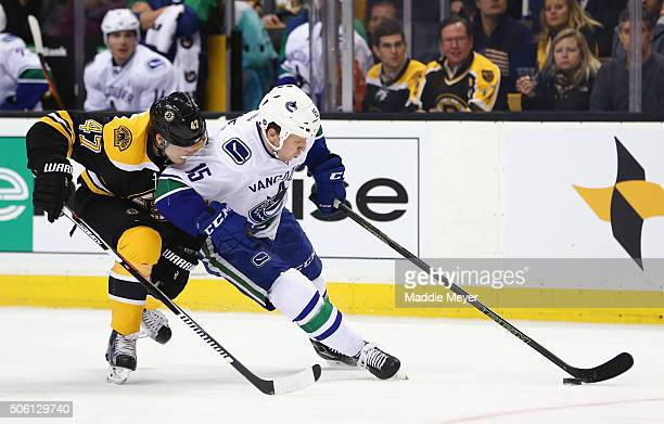 Torey Krug of the Boston Bruins and Derek Dorsett of the Vancouver Canucks battle for control of the puck during the second period at TD Garden on...