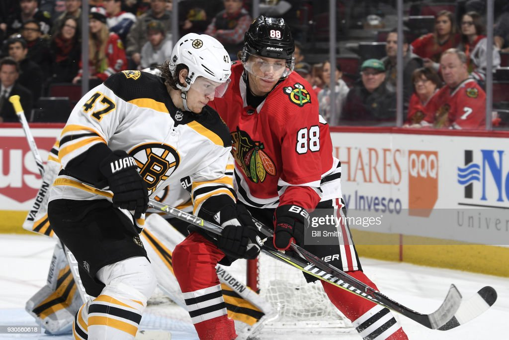 Torey Krug #47 of the Boston Bruins and Patrick Kane #88 of the Chicago Blackhawks watch for the puck in the third period at the United Center on March 11, 2018 in Chicago, Illinois.