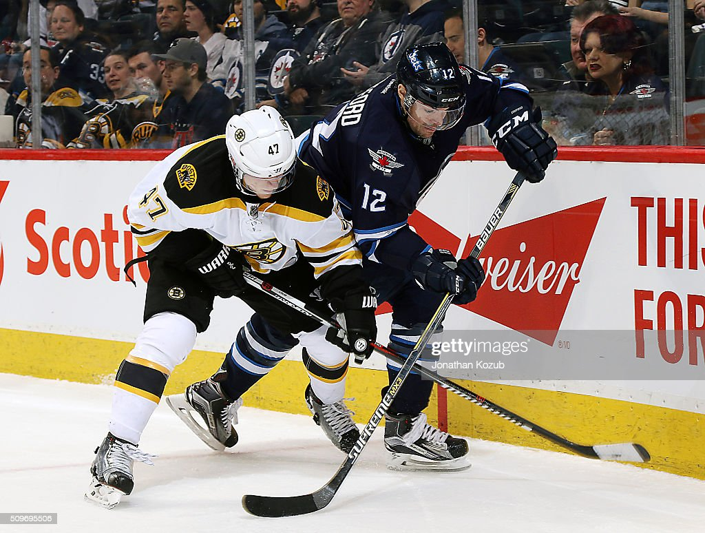 Torey Krug #47 of the Boston Bruins battles Drew Stafford #12 of the Winnipeg Jets as they follow the play along the boards during third period action at the MTS Centre on February 11, 2016 in Winnipeg, Manitoba, Canada.