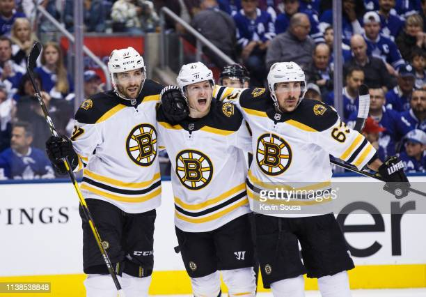 Torey Krug of the Boston Bruins celebrates his goal against the Toronto Maple Leafs with teammates Patrice Bergeron and Brad Marchand during the...