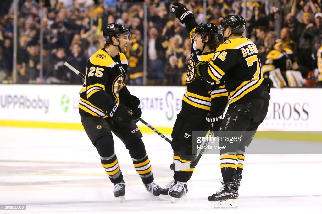 Torey Krug #47 of the Boston Bruins celebrates with Jake DeBrusk #74 and Brandon Carlo #25 after scoring a goal against the Winnipeg Jets during the third period at TD Garden on December 21, 2017 in Boston, Massachusetts. The Bruins defeat the Jets 2-1 in a shoot out.