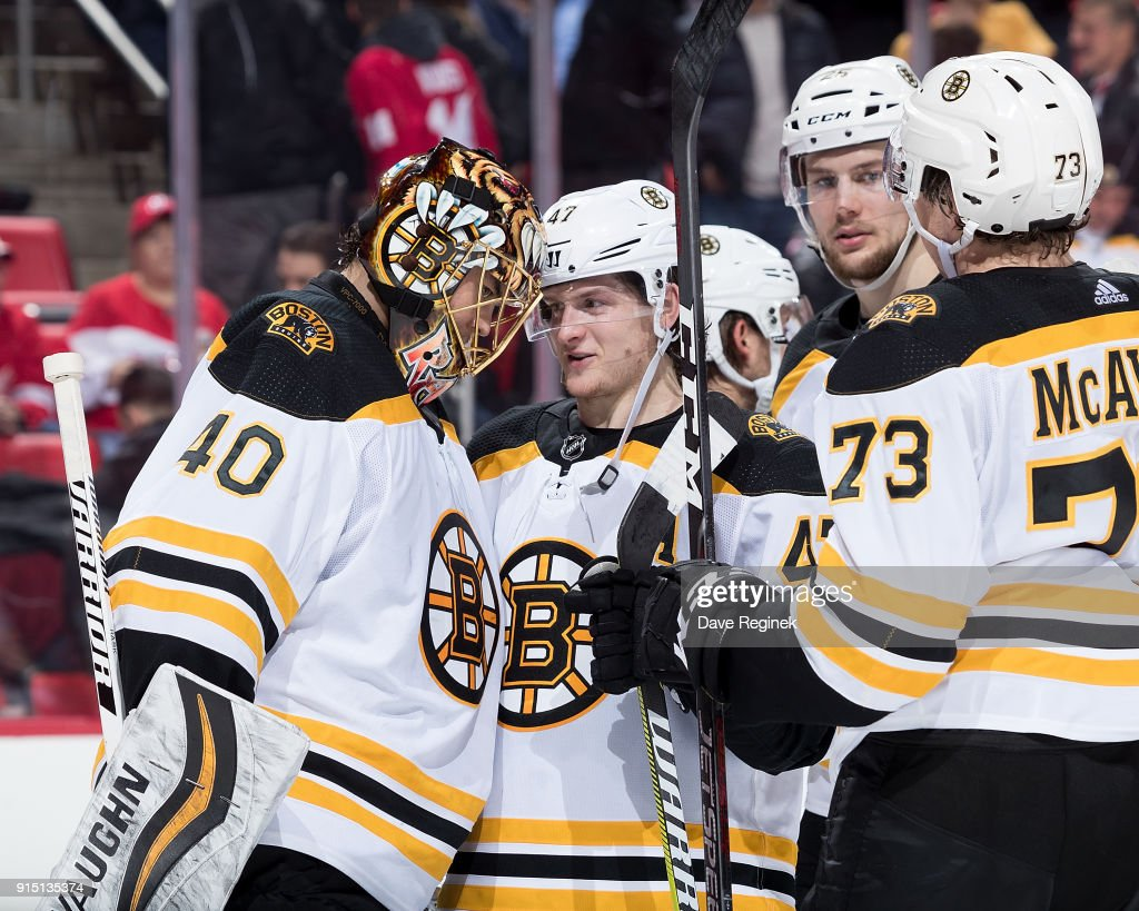 Torey Krug #47 of the Boston Bruins celebrates with teammates Tuukka Rask #40, Brandon Carlo #25 and Charlie McAvoy #73 following an NHL game against the Detroit Red Wings at Little Caesars Arena on February 6, 2018 in Detroit, Michigan. The Bruins defeated the Wings 3-2.