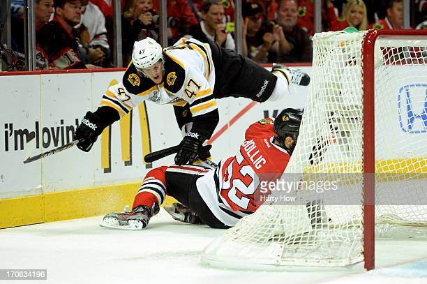 Torey Krug of the Boston Bruins falls to the ice over Brandon Bollig of the Chicago Blackhawks in Game Two of the NHL 2013 Stanley Cup Final at...