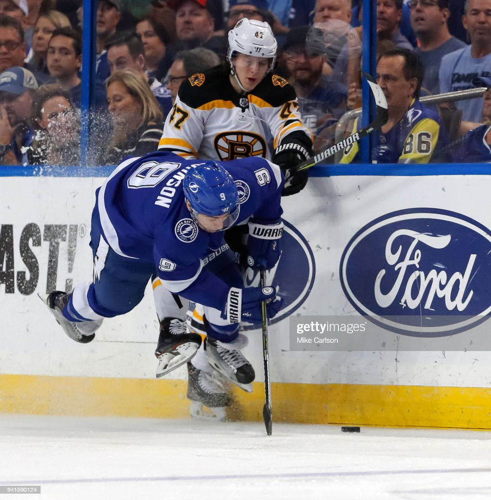 Torey Krug #47 of the Boston Bruins hits Tyler Johnson #9 of the Tampa Bay Lightning during the first period of the game at the Amalie Arena on April 3, 2018 in Tampa, Florida.