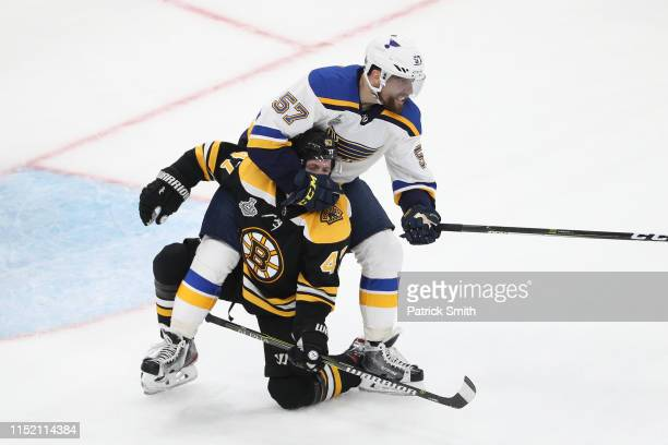 Torey Krug of the Boston Bruins is grabbed by David Perron of the St Louis Blues during the third period in Game One of the 2019 NHL Stanley Cup...