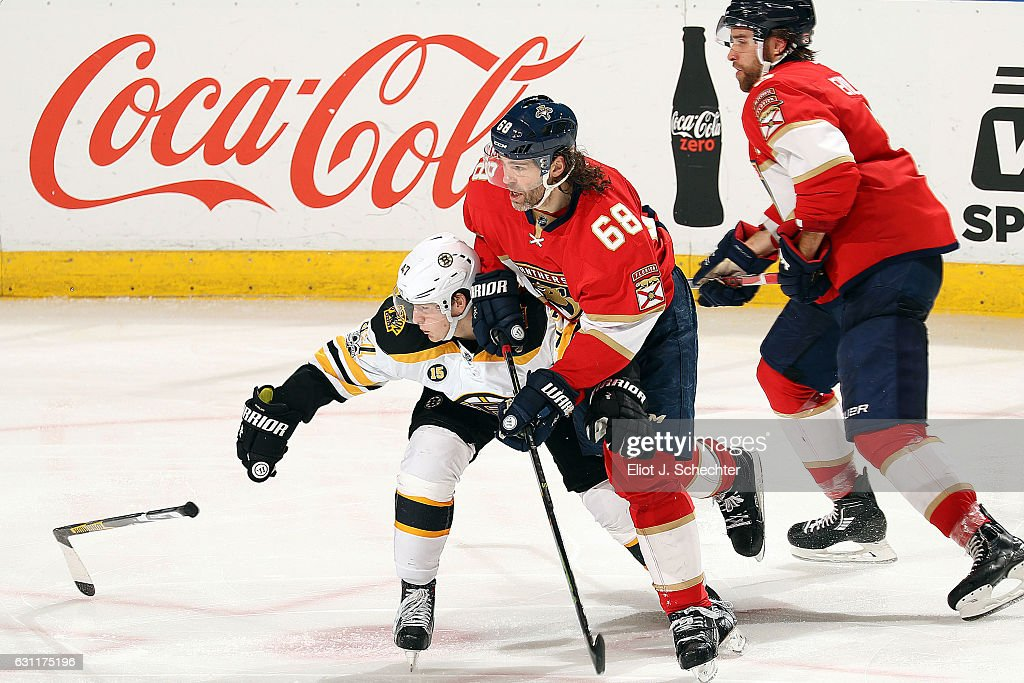 Torey Krug #47 of the Boston Bruins loses his stick in a tangle with Jaromir Jagr #68 and Aaron Ekblad #5 of the Florida Panthers at the BB&T Center on January 7, 2017 in Sunrise, Florida.
