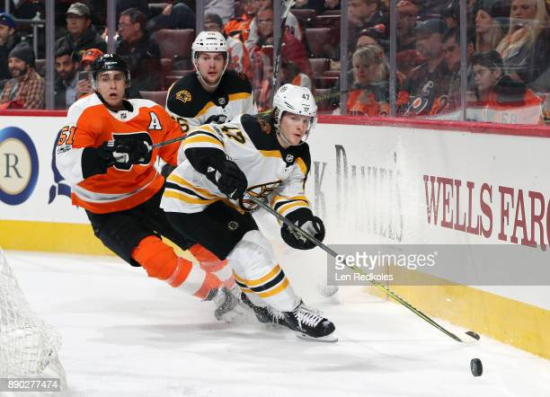 Torey Krug of the Boston Bruins passes the puck from behind the net against Valtteri Filppula of the Philadelphia Flyers on December 2 2017 at the...