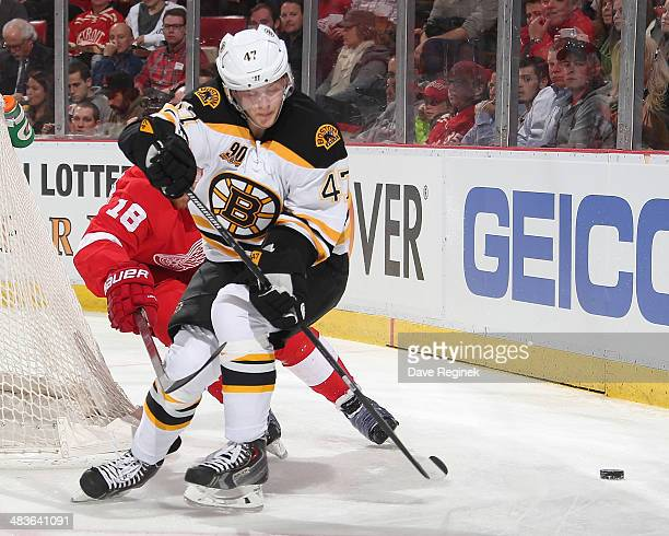 Torey Krug of the Boston Bruins passes the puck in front of Joakim Andersson of the Detroit Red Wings during an NHL game on April 2 2014 at Joe Louis...
