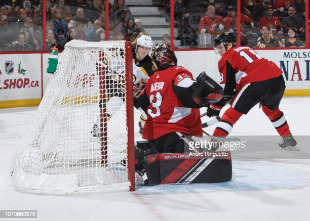 Torey Krug of the Boston Bruins scores the overtime winning goal against Mike McKenna of the Ottawa Senators as Ryan Dzingel looks on at Canadian...