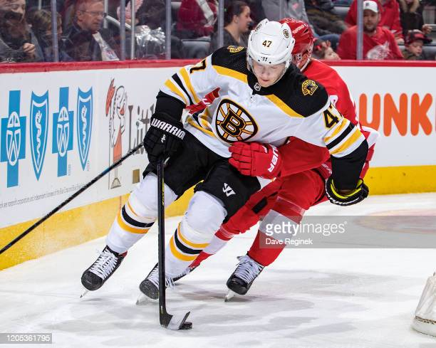 Torey Krug of the Boston Bruins skates around the net with the puck against the Detroit Red Wings during an NHL game at Little Caesars Arena on...