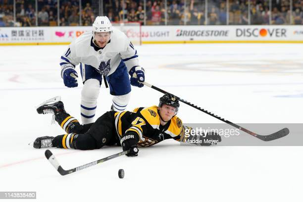 Torey Krug of the Boston Bruins slides on the ice ahead of Zach Hyman of the Toronto Maple Leafs reaching for the puck during the third period of...