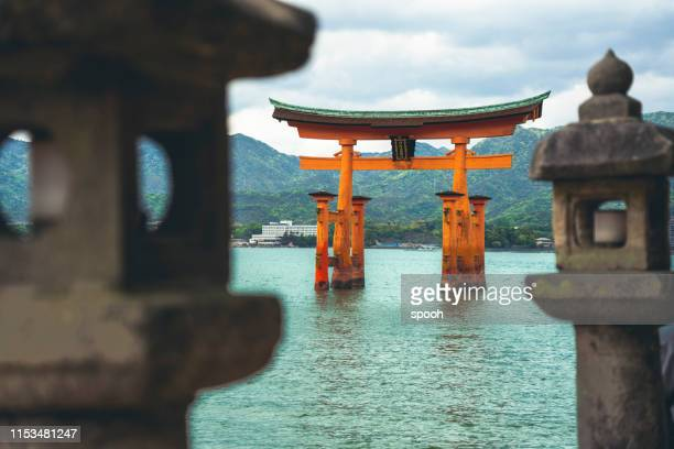 tori gate - famous buddhist shrine near miyajima island in japan - shinto shrine stock pictures, royalty-free photos & images
