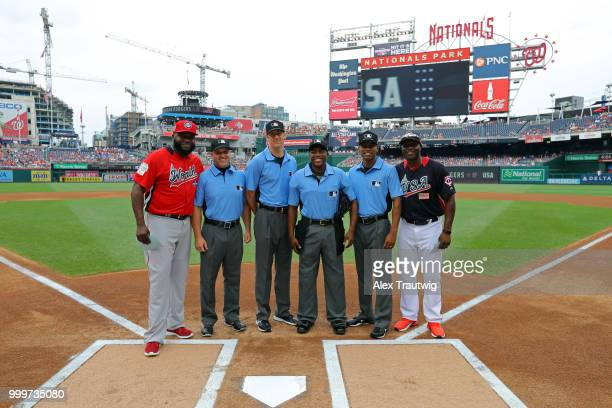 Torii Hunter of Team USA and David Ortiz of the World Team take a photo with the umpiring crew prior to the SiriusXM AllStar Futures Game at...