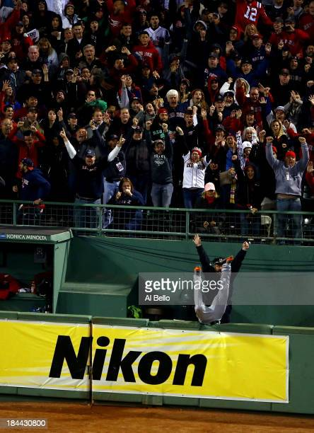 Torii Hunter of the Detroit Tigers falls over the bullpen fence after trying to catch a grand slam hit by David Ortiz of the Boston Red Sox as Boston...
