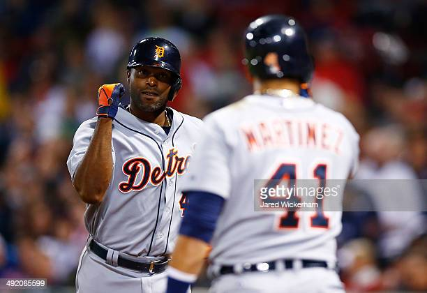 Torii Hunter of the Detroit Tigers is congratulated by teammate Victor Martinez after hitting a solo home run in the seventh inning against the...