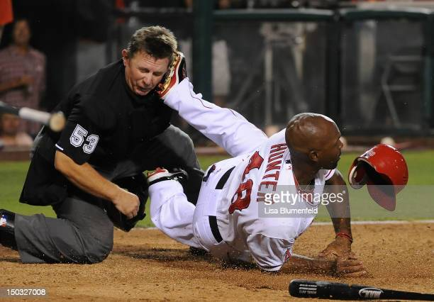 Torii Hunter of the Los Angeles Angels of Anaheim collides with umpire Greg Gibson in the fifth inning against the Cleveland Indians at Angel Stadium...