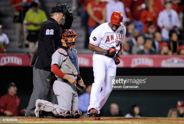 Torii Hunter of the Los Angeles Angels of Anaheim reacts to hitting a three-run home run as catcher Victor Martinez of the Boston Red Sox look on in...