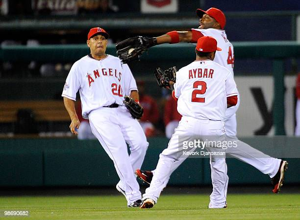 Torii Hunter of the Los Angeles of Anaheim makes a running catch between teammates Juan Rivera and Erick Aybar on a pop fly in shallow centerfield by...