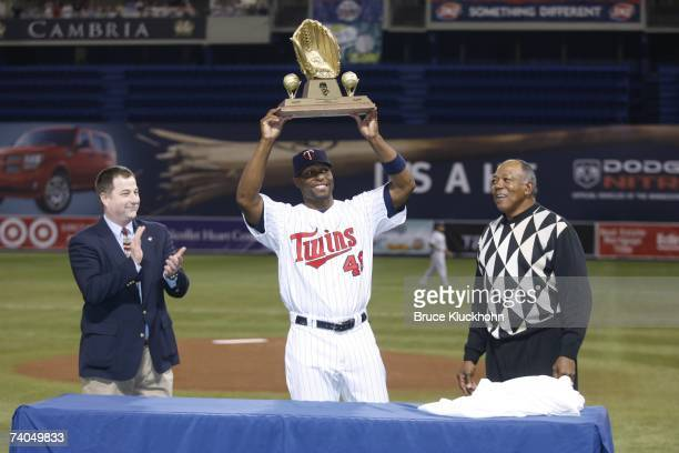 Torii Hunter of the Minnesota Twins hoists his 2006 Golden Glove award with Rawlings representative Dan Phelps and Tony Oliva in a pregame ceremony...