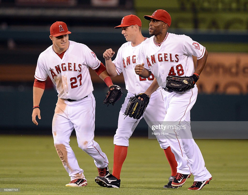 Torii Hunter #48, Peter Bourjos #25 and Mike Trout #27 of the Los Angeles Angels celebrate a 6-2 win over the Chicago White Sox at Angel Stadium of Anaheim on September 21, 2012 in Anaheim, California.