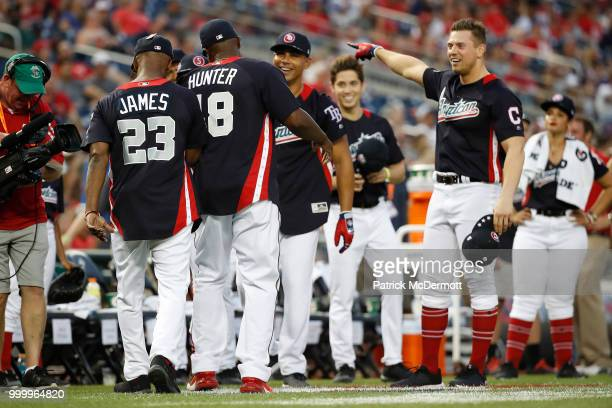 Torii Hunter walks back to the bench with Jamie Foxx during the AllStar and Legends Celebrity Softball Game at Nationals Park on July 15 2018 in...