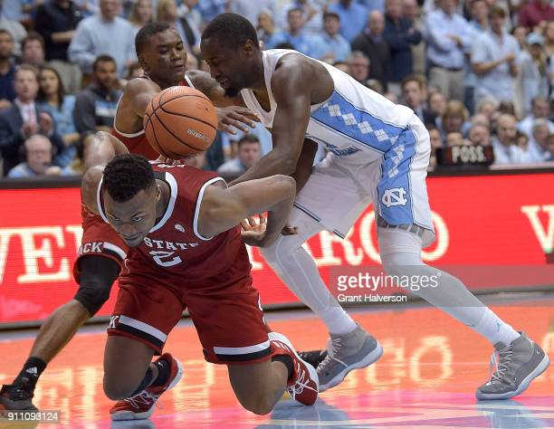 Torin Dorn and Markell Johnson of the North Carolina State Wolfpack battle Theo Pinson of the North Carolina Tar Heels for the ball during their game...