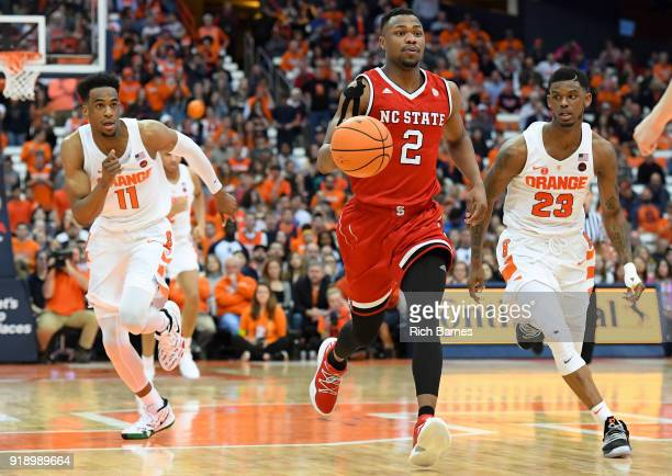 Torin Dorn of the North Carolina State Wolfpack dribbles up the court between Oshae Brissett and Frank Howard of the Syracuse Orange during the...