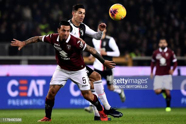 Torino's defender Armando Izzo from Italy fights for the ball with Juventus' Portuguese forward Cristiano Ronaldo during the Italian Serie A football...