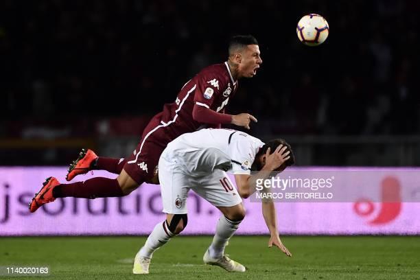 Torino's Italian defender Armando Izzo vies for the ball with AC Milan's Turkish midfielder Hakan Calhanoglu during the Italian Serie A football...
