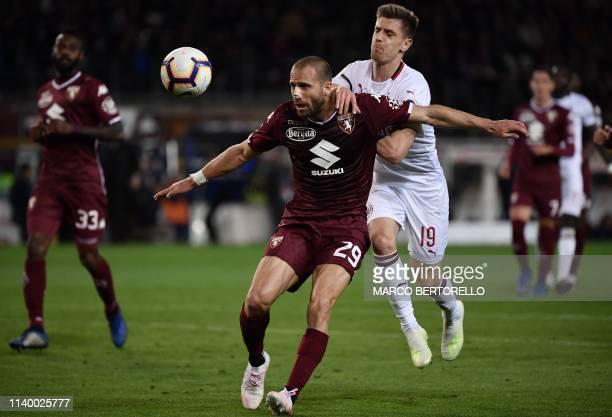 Torino's Italian defender Lorenzo De Silvestri vies for the ball with AC Milan's Polish forward Krzysztof Piatek during the Italian Serie A football...