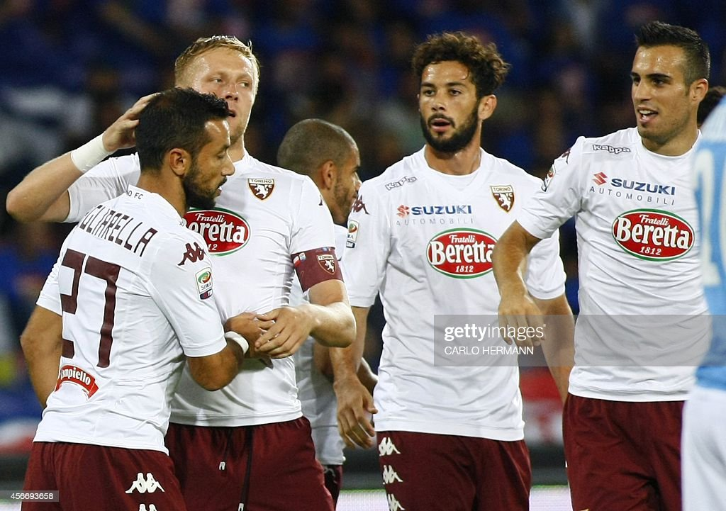 Torino's Italian forward Fabio Quagliarella (L) is congratulated by teammates after scoring a goal during the Italian Serie A football match SSC Napoli vs Torino FC on October 5, 2014 at the San Paolo stadium in Naples. HERMANN